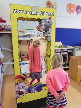 Een van de blije kinderen die geen genoeg kon krijgen van haar vervormde spiegelbeeld in de lachspiegel